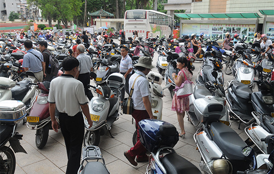 Men and women stand in crowd of mopeds
