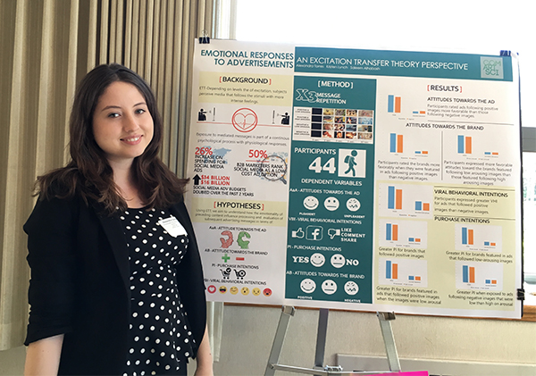 """Alexandra Torres stands next to her poster presentation, """"Emotional Responses to Advertisements."""""""