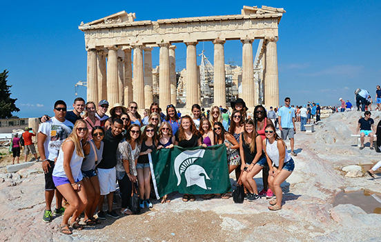 a large group of study abroad students in front of the Acropolis, holding an MSU flag