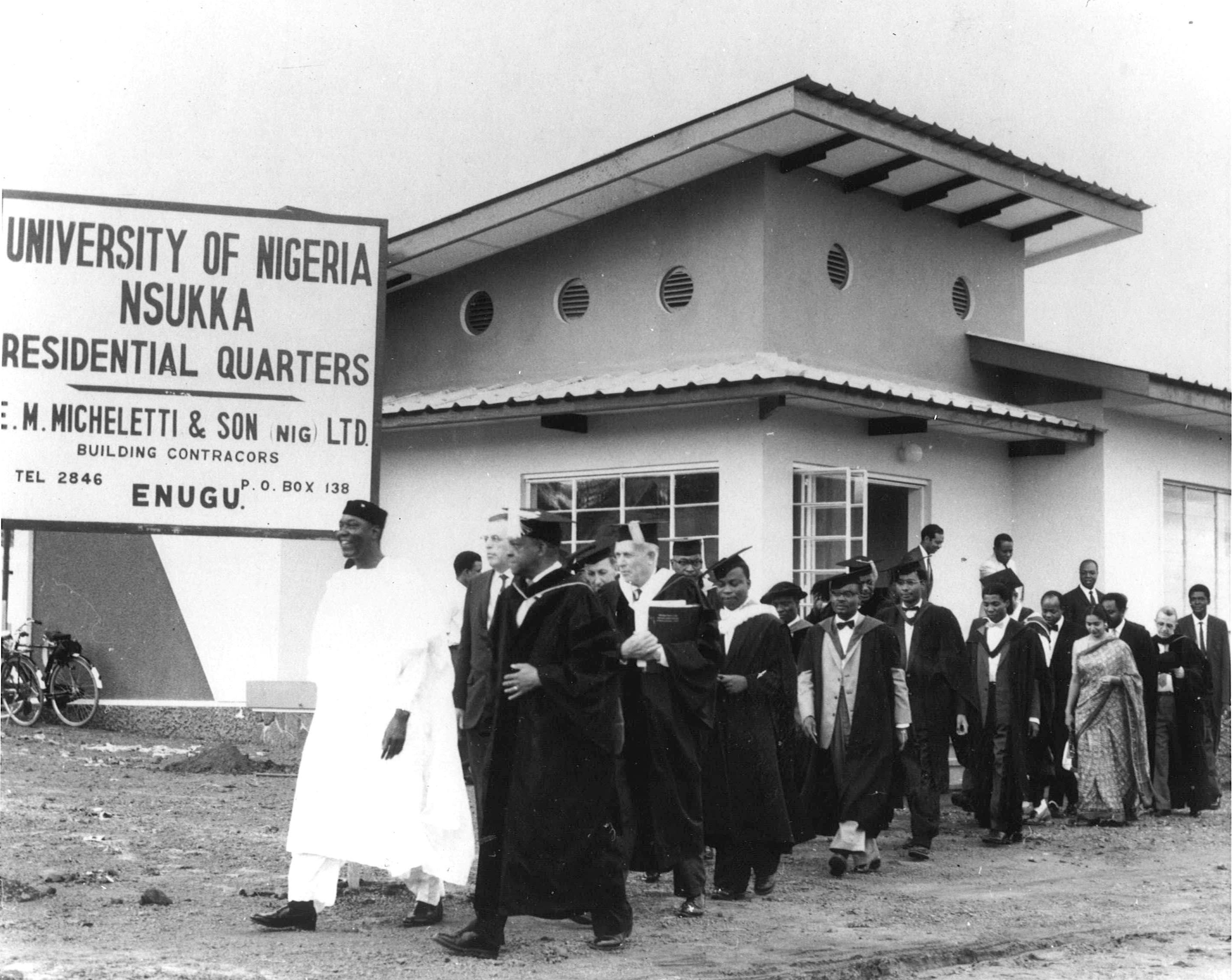 A black and white photograph taken at University of Nigeria, Nsukka. There are over a dozen men walking in academic robes in a procession outside a building.