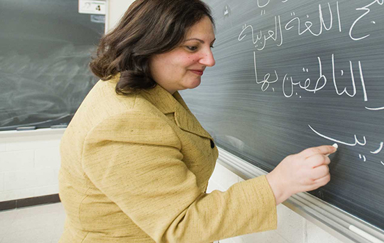 A female professor writing Arabic on a chalkboard
