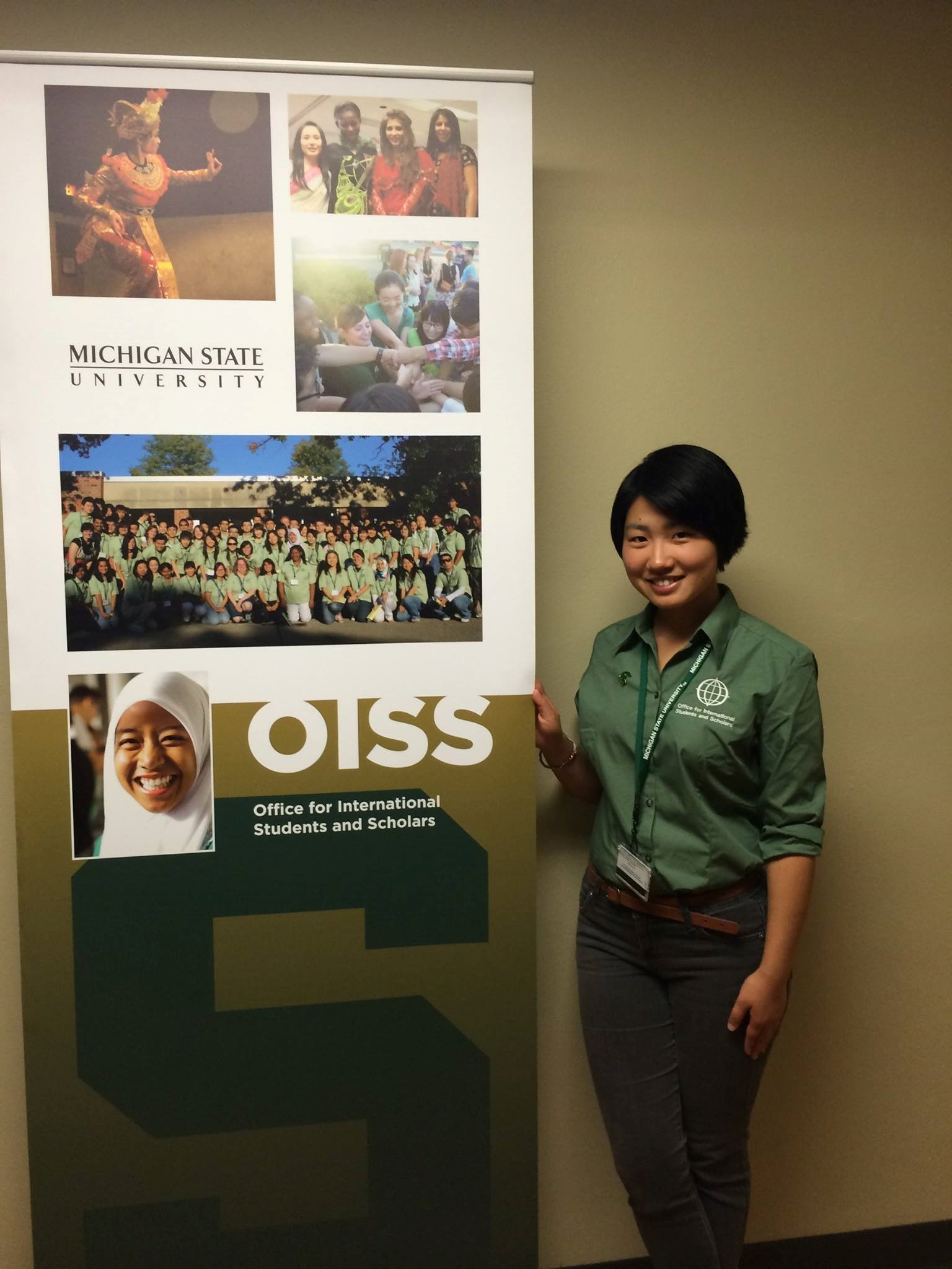 "Young woman with short black hair standing next to a vertical banner that says ""OISS Office for International Students and Scholars"" with photos of international students and a large Spartan ""S""."