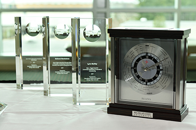 Glass awards and clock sitting on a white tablecloth