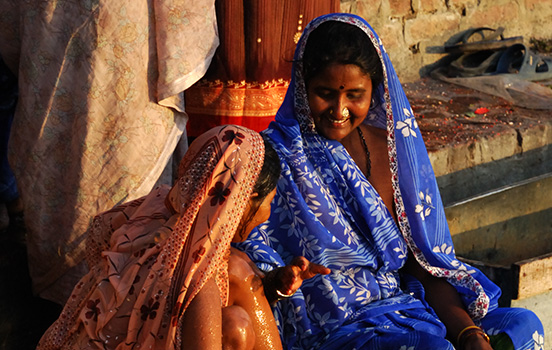 Two Indian women smiling on porch