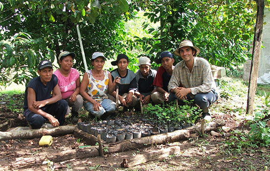 A peace corps volunteer with community members sitting around a small garden