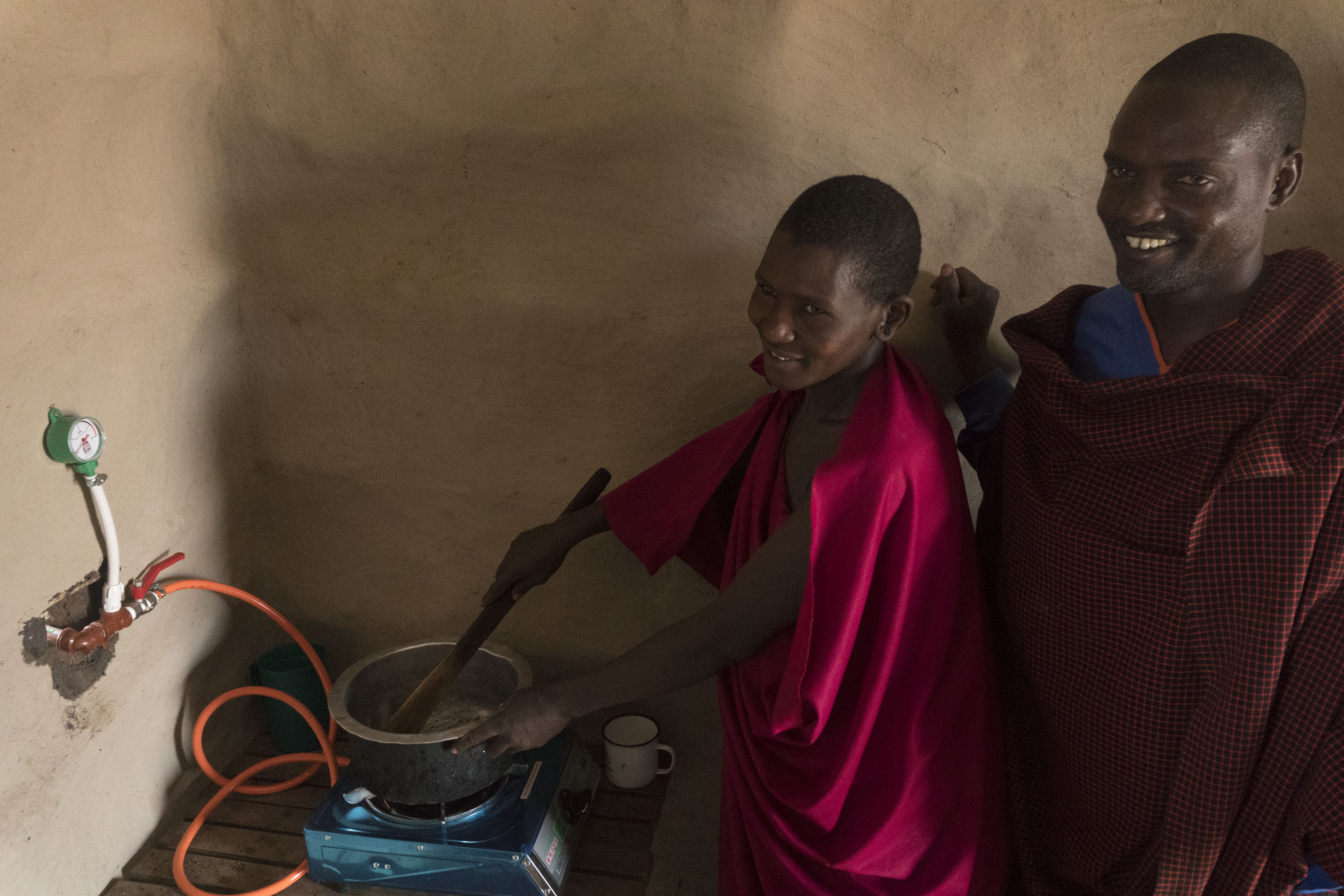 Two Naitolia village men try using the biogas stove built as a joint project between the village and the Tanzania Partnership Program group. They are inside with the small stove in the corner of the room.