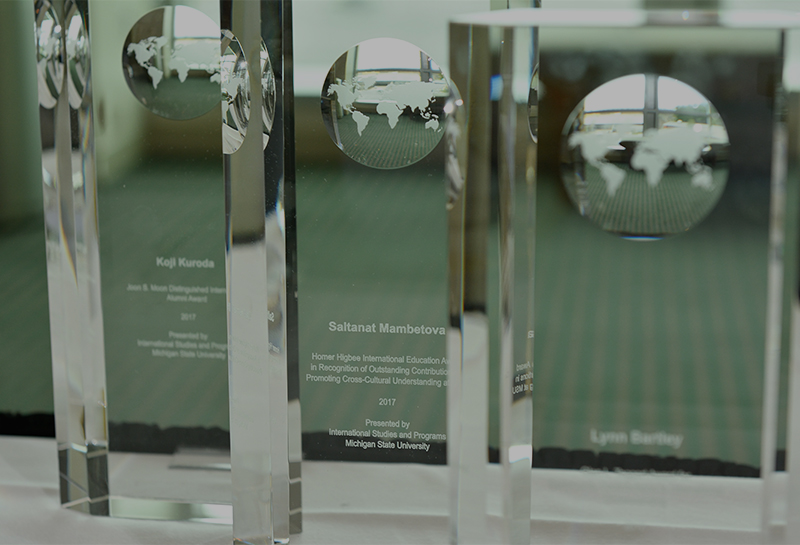 Rectangular glass awards with globes etched into them sit on a table in front of a bright window.