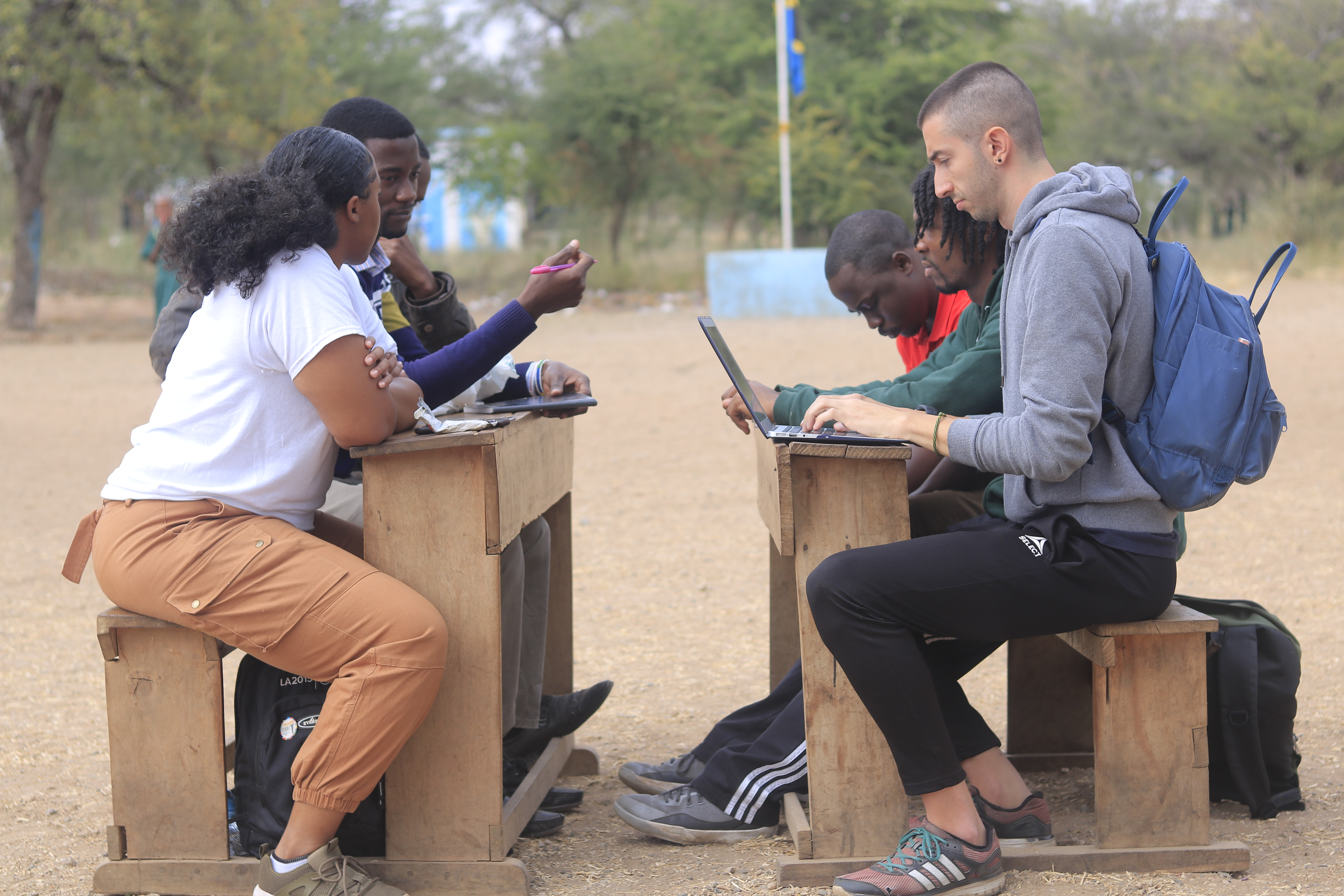 Six students sittings on wooden benches and desks outside with their laptops, papers, and pens. There are two wooden benches that face each other, with three students sitting on each side.