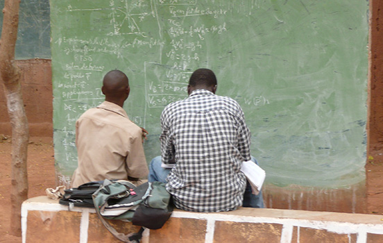 Two men study math on a chalkboard