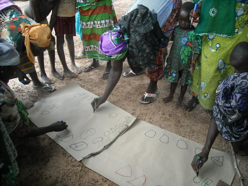 African woman bending over to write on paper placed on the ground.