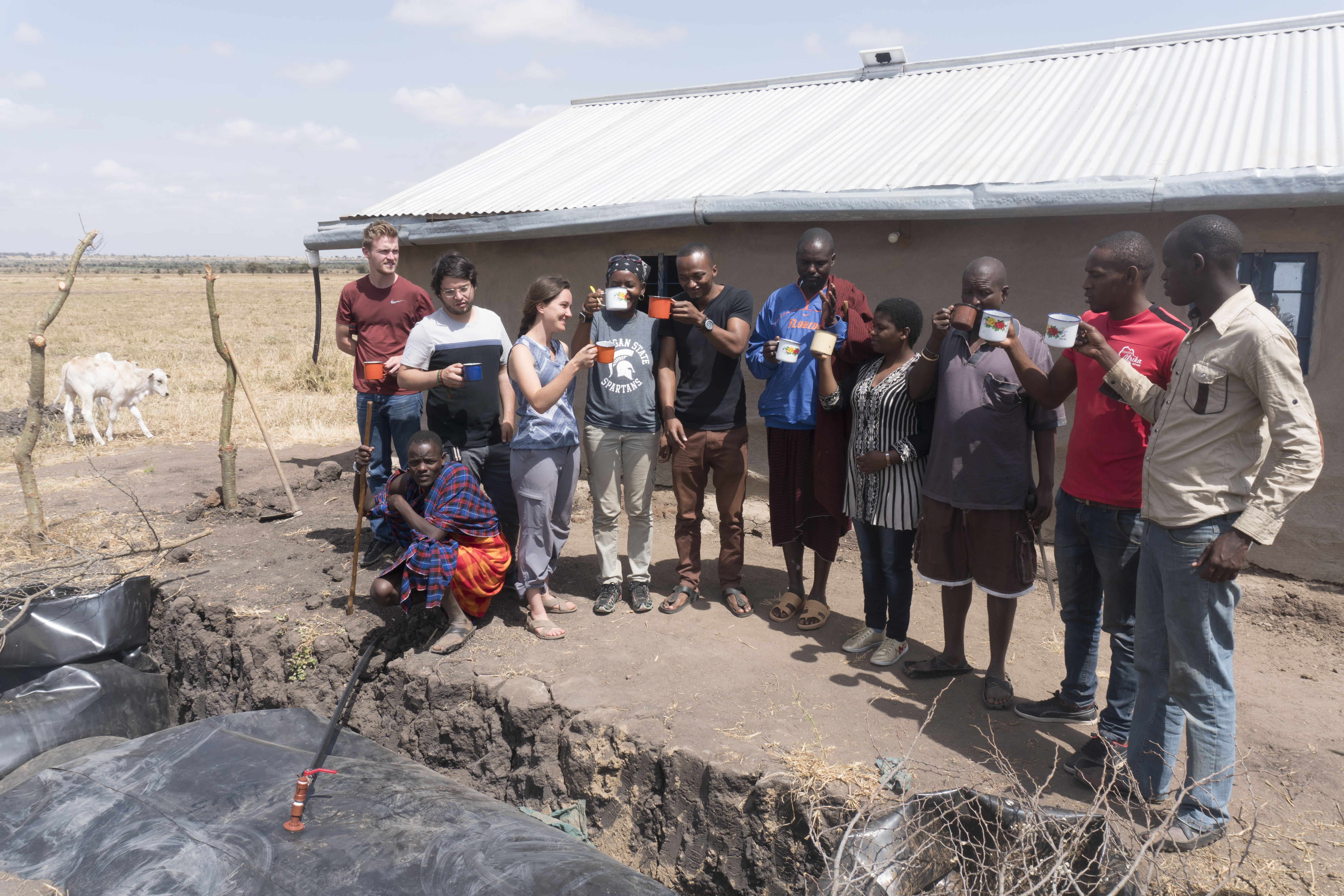 Eleven individuals are outside standing in front of the biogas system digester used to create methane gas and power the house's stove. They are standing with mugs of hot tea they made from their biogas stove.