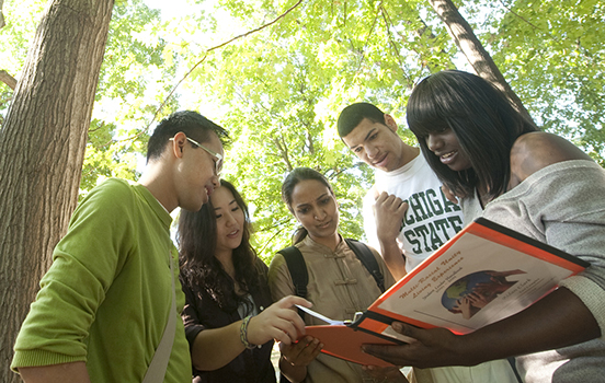 Five students outside on a sunny day looking down at a book