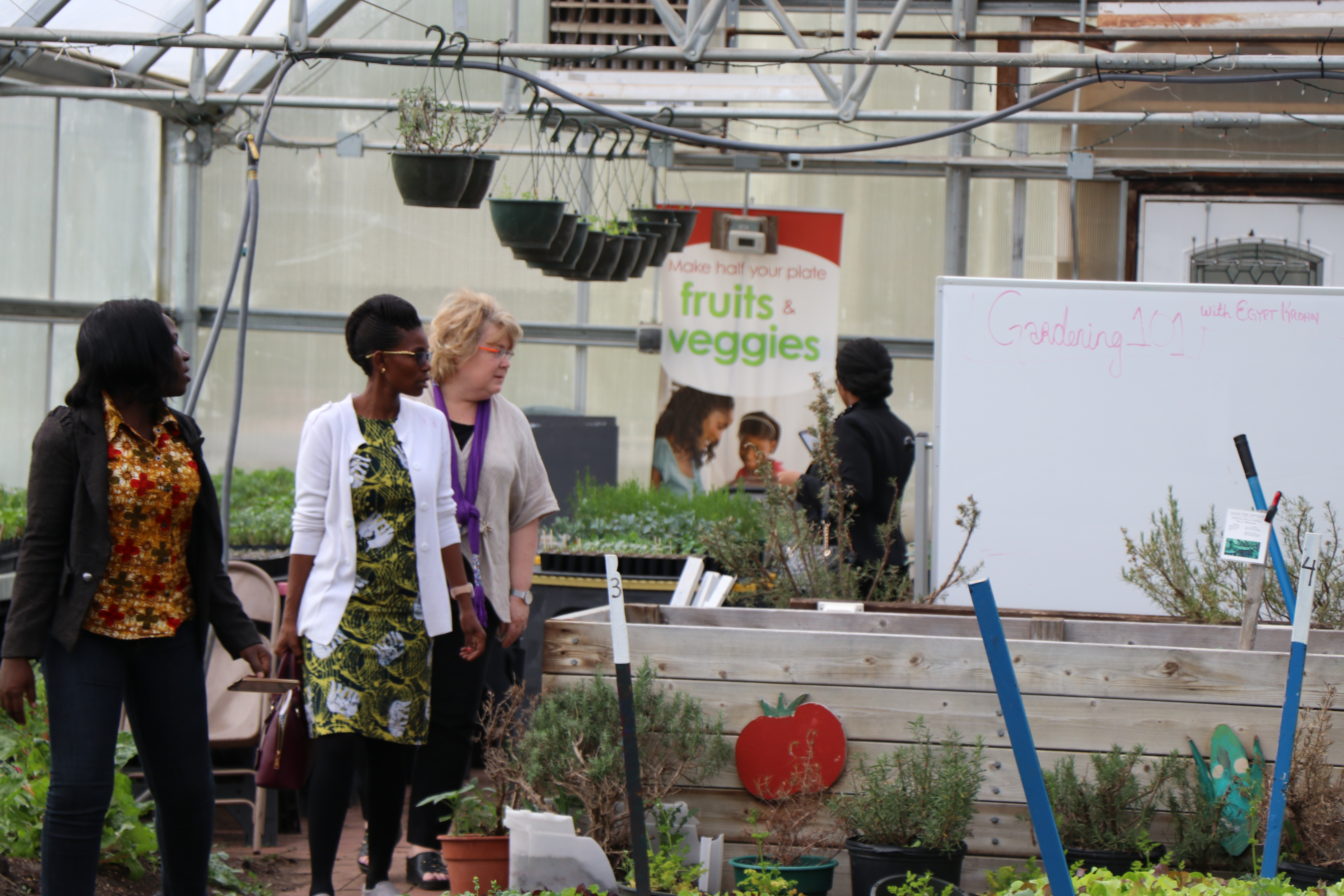 Dorcus Alowo, Christa Muzanila, and faculty member Wynne Wright in Hunter Park GardenHouse