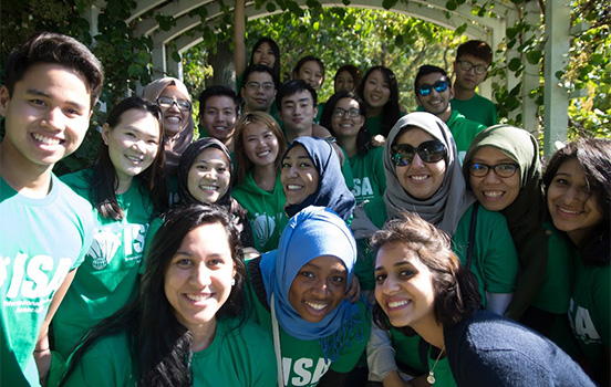 A multicultural mix of MSU students smiles at the camera