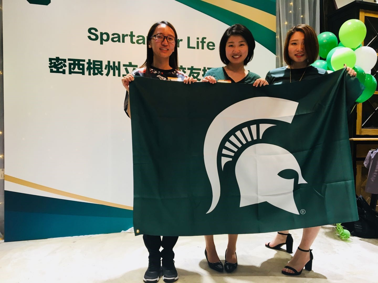 Three young women holding a large green flag with a white Spartan helmet in front of them. They are at a Michigan State University alumni reception in Shanghai, China.
